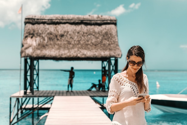 Porträt der schönen lächelnden kaukasischen frau mit lingbraunem haar, sonnenbrille und im sommerkleid unter verwendung des smartphones zum senden oder lesen der nachricht beim stehen auf pier.