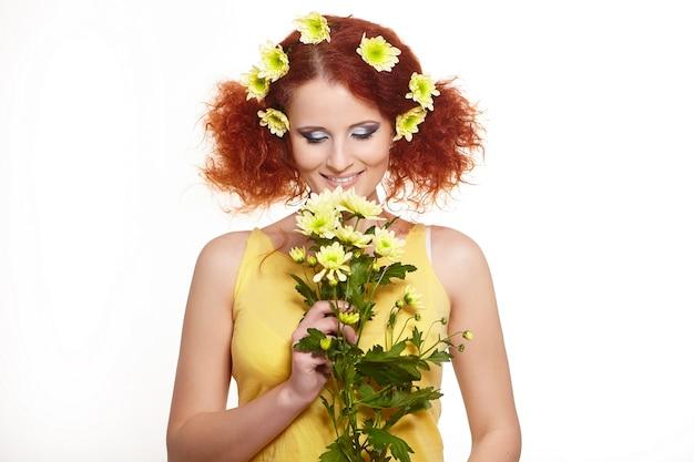 Porträt der schönen lächelnden rothaarigen ingwerfrau im gelben stoff, der gelbe blumen und blumen im haar lokalisiert auf weiß hält