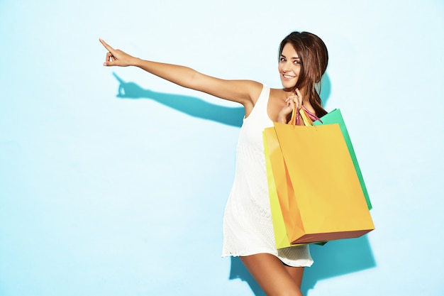 Porträt der schönen lächelnden shopaholic frau, die bunte papiertüten hält. brunettefrau, die auf blauer wand nach dem einkauf aufwirft. positives modell, das auf shopverkäufen poiting ist