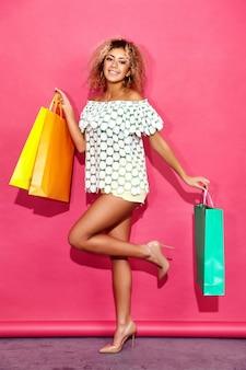 Porträt der schönen lächelnden shopaholic frau, die bunte papiertüten hält