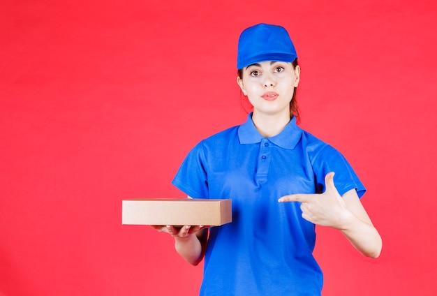 Porträt der schönen lieferfrau in blauer ausstattung, die auf karton über roter wand zeigt.