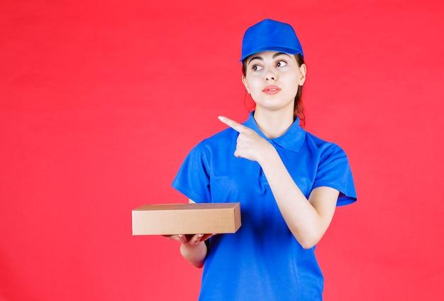 Porträt der schönen lieferfrau in der blauen ausstattung, die kartonkasten hält und zeigt.