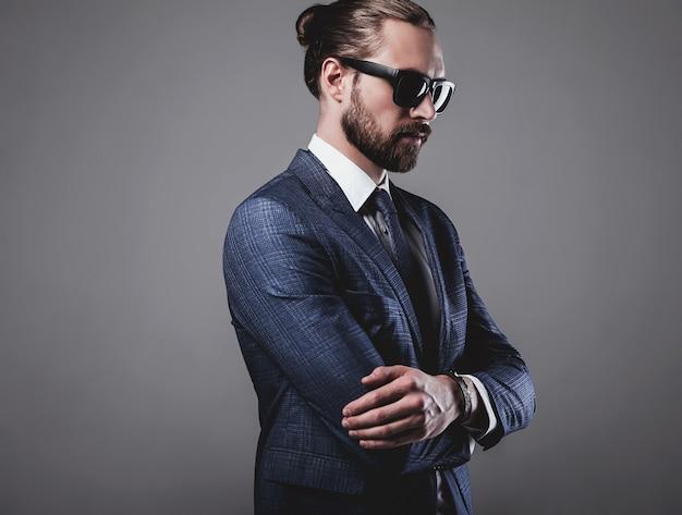Porträt der schönen mode geschäftsmann modell in eleganten blauen anzug mit sonnenbrille gekleidet
