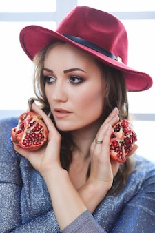 Porträt der schönen modefrau mit granatapfelfrucht