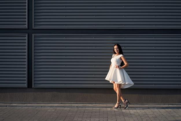 Porträt der schönen modisch gekleideten brünetten frau, die weißes stilvolles elegantes kleid aufwirft