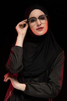 Porträt der schönen modischen jungen moslemischen frau, die schwarzes hijab und gläser als moderne ostmodekonzeptaufstellung trägt