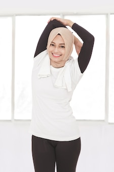 Porträt der schönen muslimischen sportlichen frau, die handdehnung tut