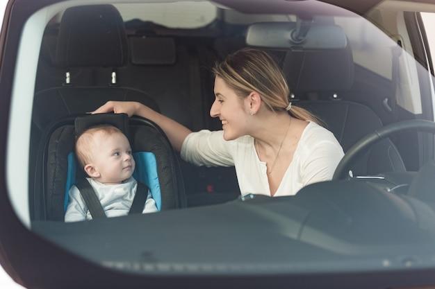 Porträt der schönen mutter bei ihrem baby, das im kindersitz am auto sitzt