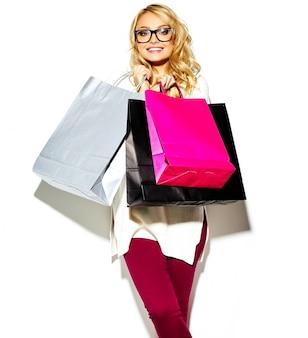 Porträt der schönen niedlichen glücklichen süßen lächelnden blonden frau frau, die in ihren händen große bunte einkaufstaschen in den hipster-kleidern lokalisiert auf weiß hält