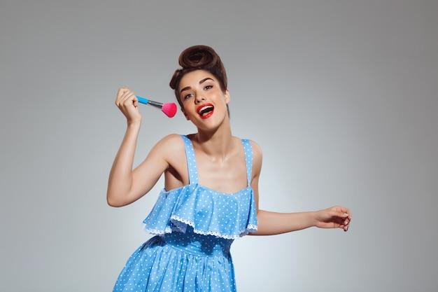 Porträt der schönen pin-up-frau, die make-up-pinsel hält