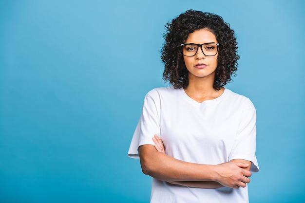 Porträt der schönen positiven afroamerikanerfrau, die mit verschränkten armen lokalisiert gegen blauen hintergrund steht.