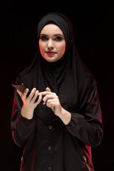 Porträt der schönen positiven freundlichen jungen moslemischen frau, die das schwarze hijab hält handy auf schwarzem hintergrund trägt