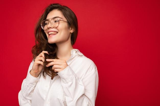 Porträt der schönen positiven fröhlichen netten lächelnden jungen brunettefrau im zufälligen weißen hemd