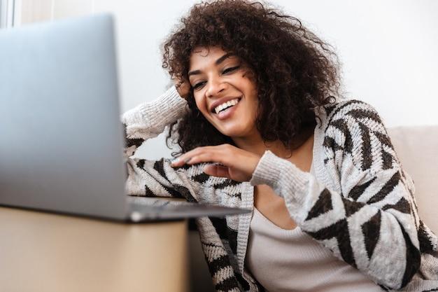Porträt der schönen positiven lächelnden jungen afrikanischen frau zuhause zu hause mit laptop-computer.