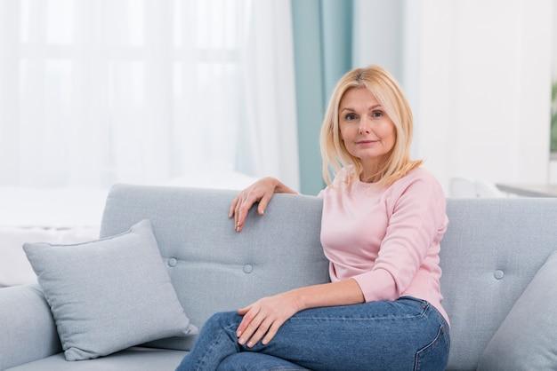 Porträt der schönen reifen frau, die auf der couch sitzt