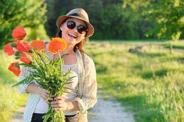 Porträt der schönen reifen gesunden glücklichen frau mit strauß der roten mohnblumen in der landschaft, kopieren raum