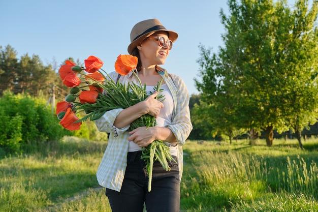 Porträt der schönen reifen gesunden glücklichen frau mit strauß der roten mohnblumen in der landschaft