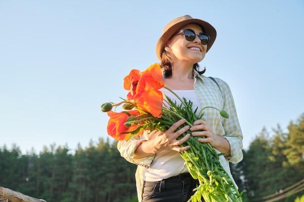 Porträt der schönen reifen gesunden glücklichen frau mit strauß der roten mohnblumen