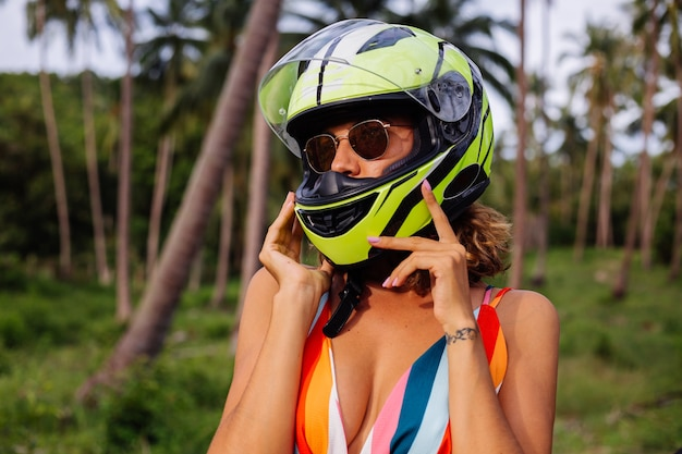 Porträt der schönen reiterin im gelbgrünen motorradhelm und im bunten hellen sommerkleid im dschungel auf tropischem feld unter palmen.