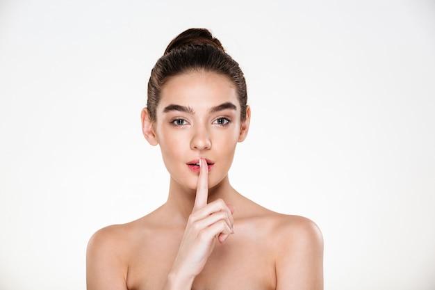 Porträt der schönen reizend jungen frau mit der perfekten haut, die zeigefinger auf den lippen bittet, ruhe zu halten