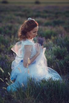 Porträt der schönen romantischen frau im märchenfeld des lavendels mit blumenstrauß