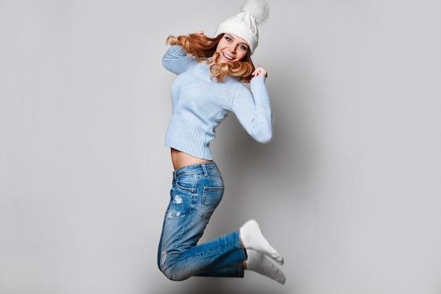 Porträt der schönen rothaarigefrau in der strickjacke