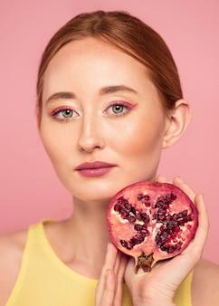 Porträt der schönen rothaarigen frau, die eine frucht hält