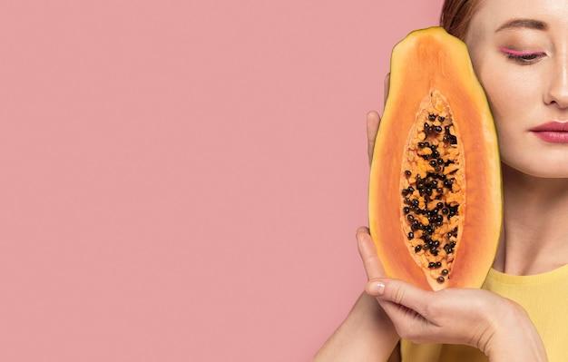 Porträt der schönen rothaarigen frau, die eine frucht mit kopienraum hält