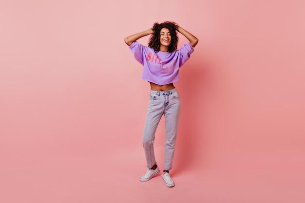 Porträt der schönen schlanken frau in voller länge, die ihr weiches schwarzes haar berührt. blithesome afrikanisches mädchen in den jeans, die auf rosig tanzen.