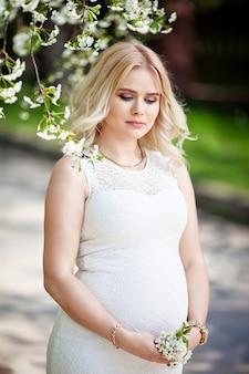 Porträt der schönen schwangeren frau im blühenden park. junge glückliche schwangere frau, die das leben in der natur genießt.