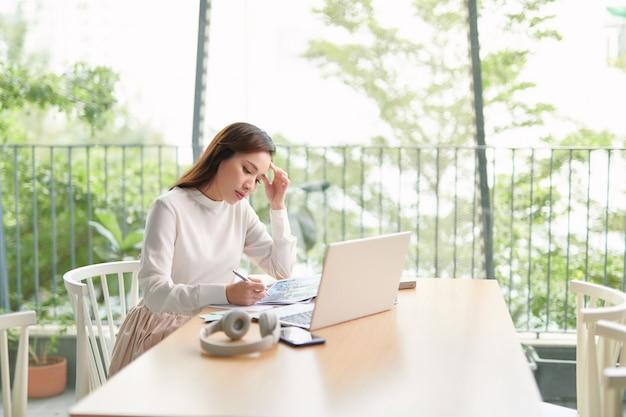 Porträt der schönen selbstbewussten frau sitzt am tisch vor dem computer