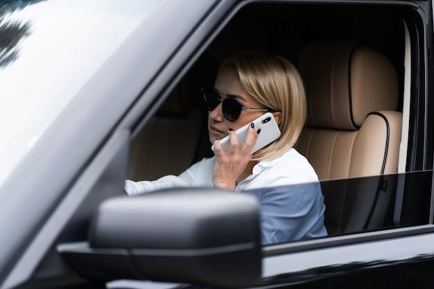Porträt der schönen sexy blonden frau in den weißen kleidern, sonnenbrille, die im dunklen luxusauto sitzt und per telefon spricht. mode- und geschäftskonzept. idee für mädchen fotoshooting mit auto.
