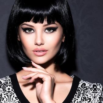 Porträt der schönen sexy frau mit hellem make-up, das am grauen hintergrund aufwirft