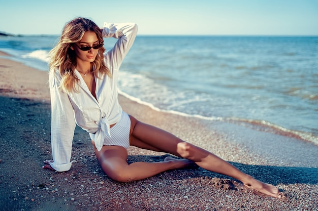 Porträt der schönen sexy kaukasischen sonnengebadeten frau in der sonnenbrille mit dem langen haar im badeanzug, der auf sommerstrand liegt