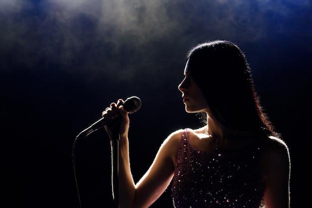 Porträt der schönen singenden frau auf dunklem hintergrund