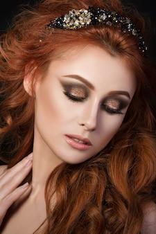 Porträt der schönen sinnlichen rothaarigen frau mit dem schwarzen haarschmuck, der nach unten schaut und ihren hals berührt
