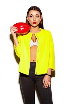 Porträt der schönen stilvollen jungen frau im gelben mantel mit roter tasche in den händen