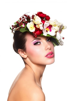 Porträt der schönen stilvollen jungen frau mit bunten blumen auf kopf