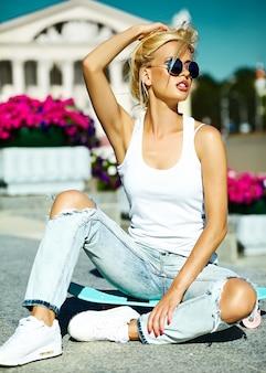 Porträt der schönen stilvollen jungen frau mit skateboard