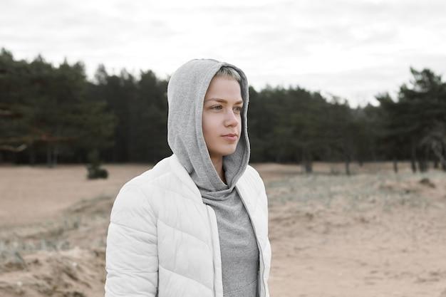 Porträt der schönen stilvollen jungen kaukasischen frauenhaube und der weißen jacke, die auf verlassenem sandstrand während der ferien auf see gehen. konzept für freizeit, entspannung, aktivität, menschen und lebensstil