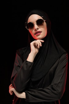 Porträt der schönen stilvollen jungen moslemischen frau, die schwarze hijab und sonnenbrille trägt, arbeiten die konzeptaufstellung um