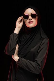 Porträt der schönen stilvollen jungen moslemischen frau, die schwarzes hijab und sonnenbrille als moderne ostmodekonzeptaufstellung trägt