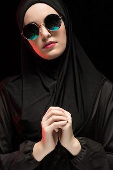 Porträt der schönen stilvollen jungen moslemischen frau, die schwarzes hijab und sonnenbrille als modernes ostmodekonzept auf schwarzem hintergrund trägt
