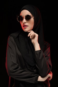 Porträt der schönen stilvollen jungen moslemischen frau, die schwarzes hijab und sonnenbrille als modernes ostmodekonzept aufwirft auf schwarzem hintergrund trägt