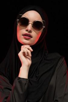 Porträt der schönen stilvollen jungen moslemischen frau, die schwarzes hijab und sonnenbrille trägt