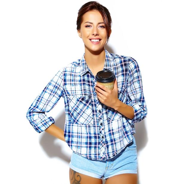 Porträt der schönen stilvollen kühlen lustigen jugendfrau, die im karierten hemd, plastikkaffeetasse halten verrückt geht