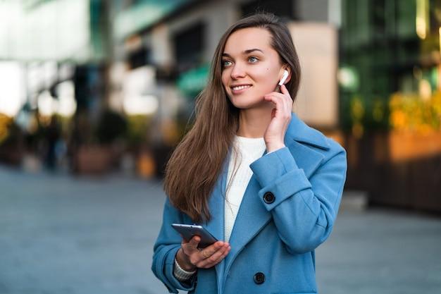 Porträt der schönen stilvollen trendigen glücklichen freudigen brünetten frau in einem blauen mantel mit kabellosen weißen kopfhörern und handy im stadtzentrum. moderne menschen und technologie