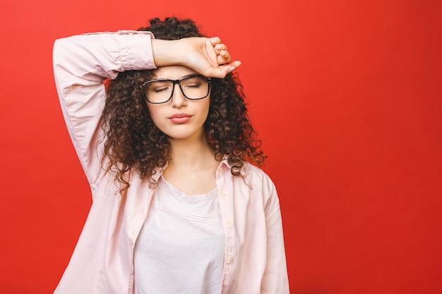 Porträt der schönen studentenfrau müde bei der arbeit, lokalisiert auf einem roten hintergrund.