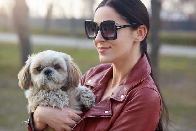 Porträt der schönen süßen reizenden frau, die lederjacke und sonnenbrille trägt, draußen mit ihrem hund ist, freien tag mit haustier verbringt, spazieren geht, auf der straße steht.