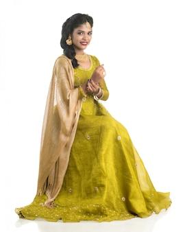 Porträt der schönen traditionellen indischen frau, die auf weißer wand aufwirft.